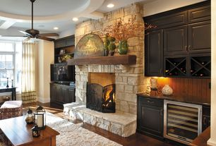 Country Living Room with Ceiling fan, stone fireplace, Built-in bookshelf, Hardwood floors