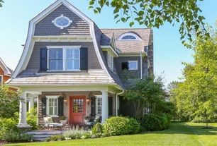 Craftsman Exterior of Home with Exterior shutters, Bushes, Covered porch, Wrap around porch, Lawn, Red front door