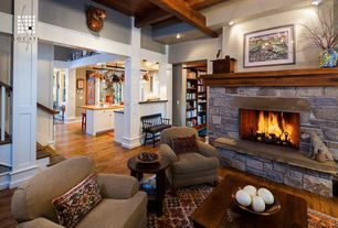 Craftsman Living Room with Hardwood floors, stone fireplace, York roll arm upholstered armchair, High ceiling, Exposed beam