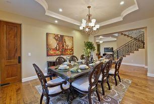 Traditional Dining Room with Crown molding, specialty door, can lights, Standard height, Chandelier, Hardwood floors