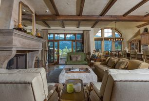 Mediterranean Great Room with Hardwood floors, Cement fireplace, Exposed beam, Built-in bookshelf, French doors