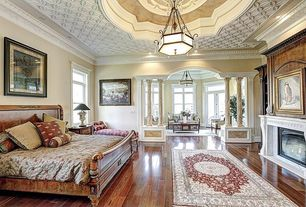 Traditional Master Bedroom with High ceiling, Columns, French doors, Crown molding, Hardwood floors, Chandelier
