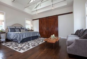 Contemporary Master Bedroom with Exposed beam, Hardwood floors, Skylight, Pendant light, High ceiling, Barn door
