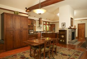 Craftsman Dining Room with stone fireplace, can lights, Hardwood floors, Exposed beam, Standard height, Crown molding