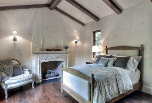 Traditional Guest Bedroom with High ceiling, Hardwood floors, Paint, Exposed beam, Fireplace, Wall sconce, Cement fireplace