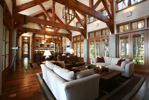 Craftsman Great Room with Wall sconce, Cathedral ceiling, Pendant light, Built-in bookshelf, French doors, Columns