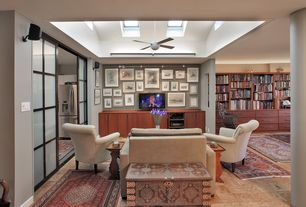 Contemporary Living Room with Suffolk Chair, Antique White, Ceiling fan, Skylight, Hardwood floors, Built-in bookshelf