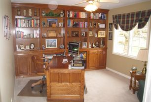 Traditional Home Office with Casement, Carpet, Ceiling fan, Built-in bookshelf, Standard height