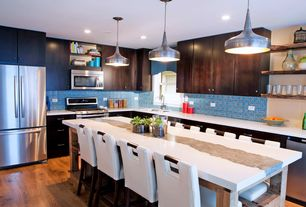 Eclectic Kitchen with full backsplash, Kitchen island, built-in microwave, Corian counters, double-hung window, Flush
