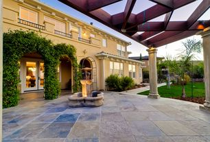 Mediterranean Landscape/Yard with Pathway, Fountain, Fence, Arbor, picture window, exterior stone floors, French doors
