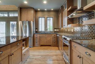 Craftsman Kitchen with can lights, gas range, Kitchen island, European Cabinets, Flush, Glass Tile, Multiple Refrigerators
