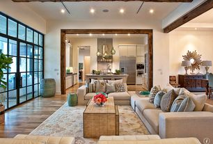 Contemporary Living Room with Chateau round sunburst mirror, French doors, Exposed beam, Hardwood floors, Colored vintage rug