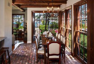 Traditional Dining Room with double-hung window, Sun room, Exposed beam, Chandelier, Standard height, Brick floors