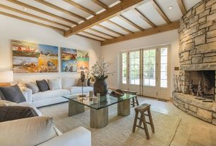 Contemporary Living Room with limestone tile floors, French doors, stone fireplace, Exposed beam