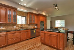 Traditional Kitchen with full backsplash, Framed Partial Panel, Undermount sink, electric cooktop, double wall oven, Casement