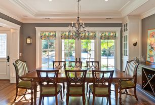 Traditional Dining Room with Crown molding, Built-in bookshelf, Hardwood floors, French doors, Chandelier, Wall sconce