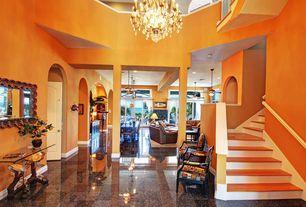 Tropical Entryway with Columns, Balcony, simple granite tile floors, specialty door, Chandelier, High ceiling