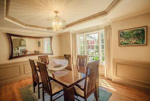 Traditional Dining Room with interior wallpaper, Wainscotting, Hardwood floors, Standard height, flush light, Crown molding