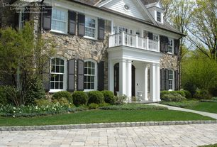Traditional Exterior of Home with Stone exterior cladding, Exterior shutters, Columns, Arched windows, Exterior paint