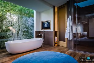 Modern Master Bathroom with Wyndham Collection Melissa Free Standing Soaking Bathtub, Hardwood floors, specialty door
