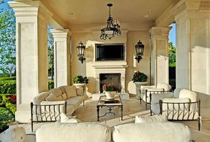 Mediterranean Patio with Hinkley black beveled glass manor house wall sconce, Outdoor seating, Stone columns, Raised beds