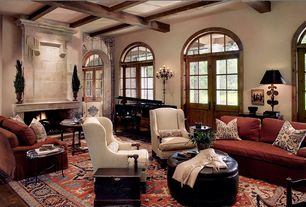 Traditional Living Room with interior brick, Arched window, Hardwood floors, Fireplace, Exposed beam, French doors