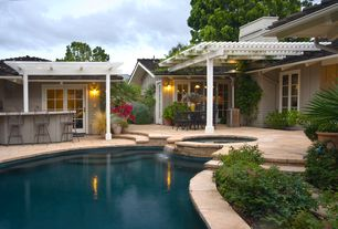Traditional Swimming Pool with Outdoor kitchen, exterior stone floors, Trellis, Pool with hot tub, French doors