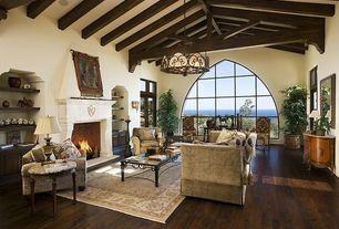 Mediterranean Living Room with Hardwood floors, Built-in bookshelf, Chevron brick pattern, Arched window, Gothic paned window