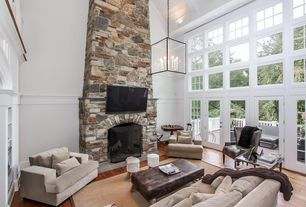 Traditional Living Room with Built-in bookshelf, Wainscotting, Hardwood floors, Chandelier, French doors, stone fireplace