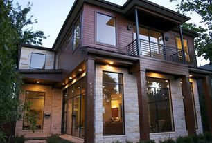 Contemporary Exterior of Home with Wall sconce, Exposed brick wall, Glass panel door, Transom window, Covered balcony, Fence