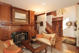 Traditional Living Room with Crown molding, Built-in bookshelf, stone fireplace, Hardwood floors