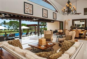 Tropical Great Room with Pier 1 graciosa wing chair, sandstone floors, Kichler lighting 9 light willowmore chandelier