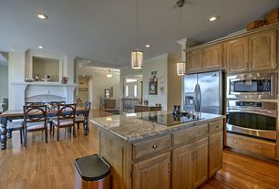 Traditional Dining Room with Side by side refrigerator, Hardwood floors, Dining table, stone fireplace, Pendant light