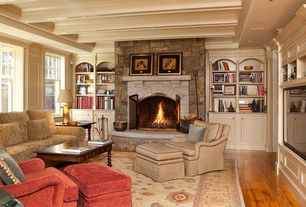 Traditional Living Room with Crown molding, Hardwood floors, Built-in bookshelf, stone fireplace, Exposed beam