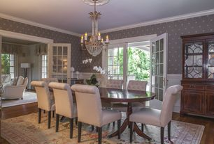Traditional Dining Room with Margaux oval dining table set, Wainscotting, interior wallpaper, Chandelier, French doors