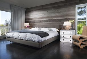 Contemporary Master Bedroom with Frank gehry wiggle chair, can lights, Hardwood floors, Reclaimed wood plank wall