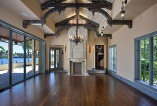 Traditional Living Room with Hardwood floors, Exposed beam, Cement fireplace, High ceiling, Pendant light, Chandelier