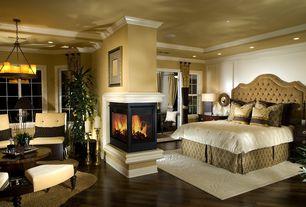 Contemporary Master Bedroom with Cement fireplace, Veranda round chandelier, Crown molding, metal fireplace, Hardwood floors