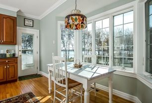 Traditional Dining Room with Pendant light, Built-in bookshelf, Crown molding, Hardwood floors, French doors