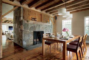 Country Dining Room with stone fireplace, Built-in bookshelf, Pendant light, Standard height, Hardwood floors, Casement