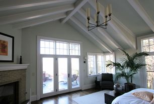 Traditional Master Bedroom with brick fireplace, Chandelier, Casement, Exposed beam, can lights, French doors, Fireplace
