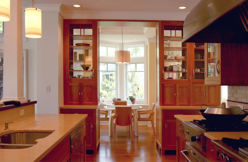Craftsman Kitchen with dishwasher, Simple marble counters, Crown molding, Urbia - naturals old wood arm chair, gas range