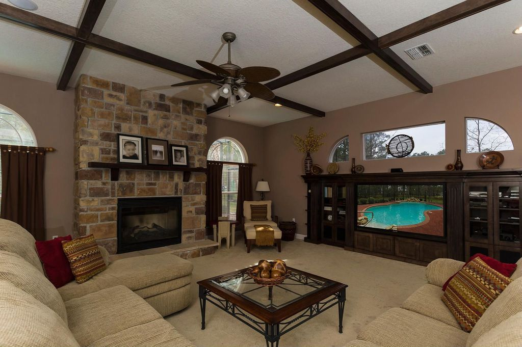 Contemporary Family Room with Standard height, L-shaped sectional sofa, stone fireplace, Carpet, Arched window, Exposed beam