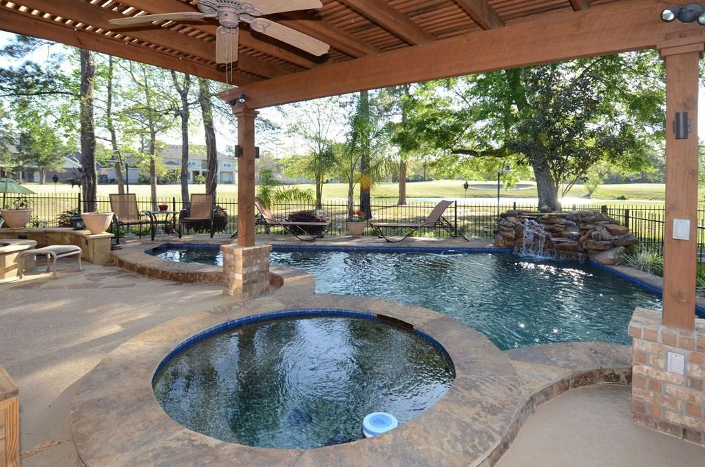 Rustic Swimming Pool with Trellis, exterior tile floors, Fence, Fire pit, exterior concrete tile floors, Pool with hot tub