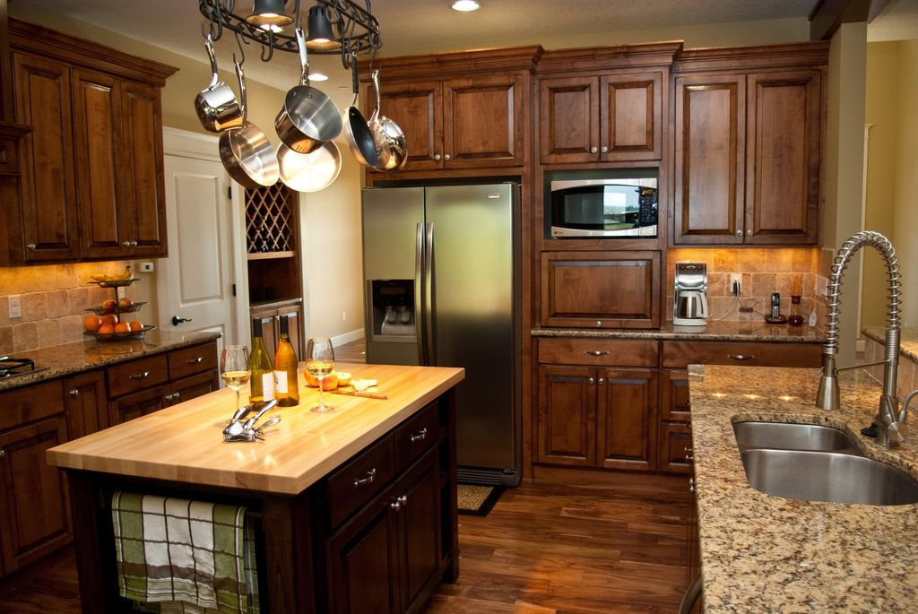 Traditional Kitchen with Built In Refrigerator, Wood counters, dishwasher, Stone Tile, Simple granite counters, Raised panel