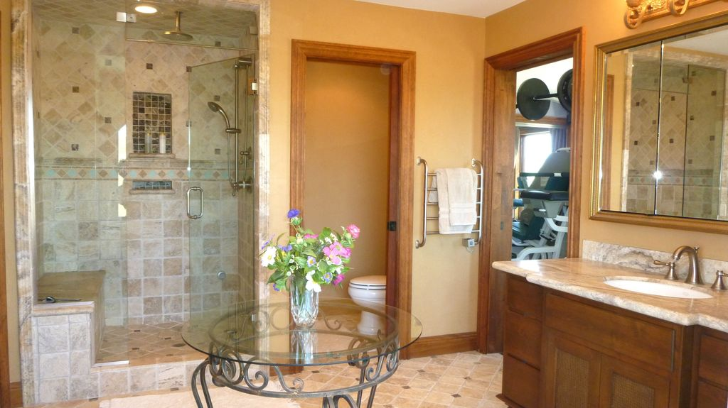 Craftsman 3/4 Bathroom with wall-mounted above mirror bathroom light, Shower, stone tile floors, Inset cabinets, Rain shower
