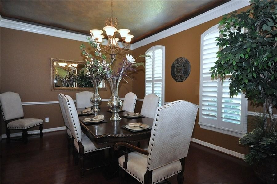 Eclectic Dining Room with Chandelier, Standard height, Laminate floors, Crown molding, Chair rail, Casement