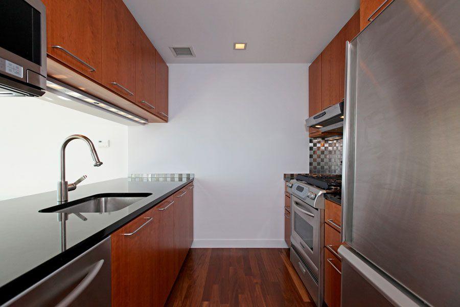 Contemporary Kitchen with Flush, Soapstone counters, Hardwood floors, gas range, partial backsplash, Wall Hood, Glass Tile