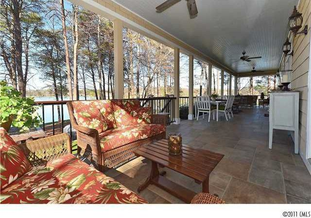Traditional Porch with exterior stone floors, Water view, Deck Railing, Columns, Outdoor ceiling fan, Wrap around porch