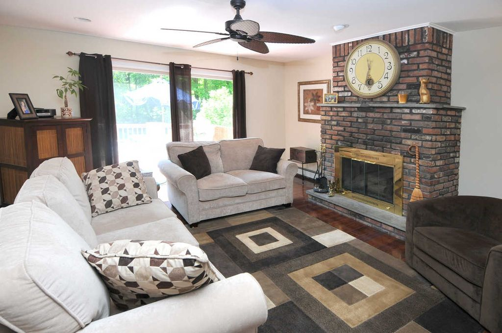 Eclectic Living Room with sliding glass door, Ceiling fan, Hardwood floors, Fireplace, Standard height, brick fireplace
